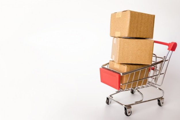 Caixas ou caixas de papel no carrinho de compras vermelho no fundo branco. com espaço para texto Foto Premium
