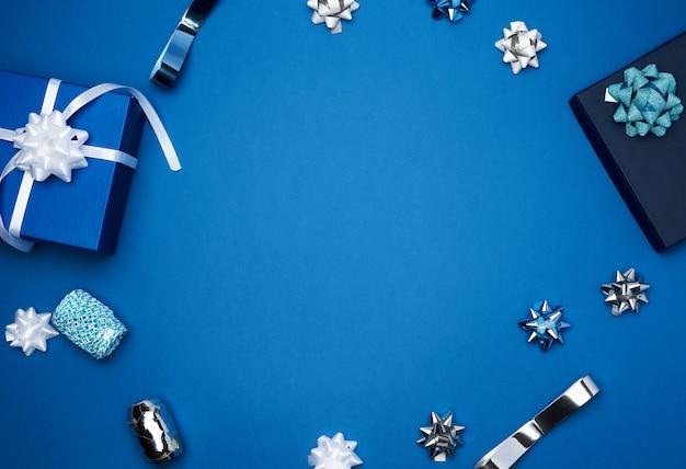 Caixas quadradas de presente de papelão, arcos, fitas para embalagem em um azul escuro Foto Premium