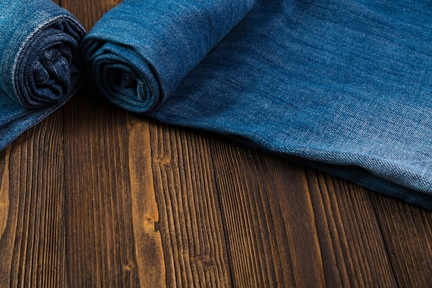 Calça jeans roll frayed ou jeans azul em madeira escura áspera Foto Premium