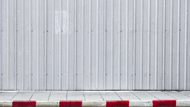 Calçada e meio-fio vermelho-branco com parede de metal corrugado Foto Premium