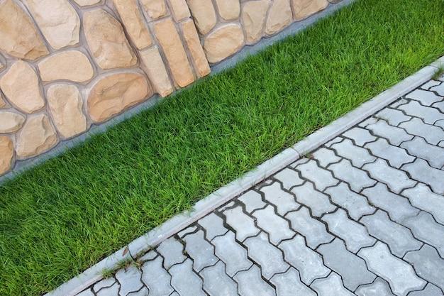 Calçada pavimentada com tijolos de cimento e gramado com grama verde Foto Premium