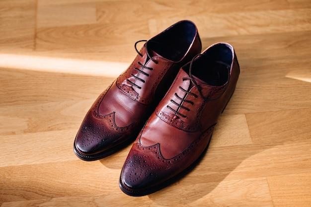 Calçados de couro vermelho estão no chão de madeira clara Foto gratuita