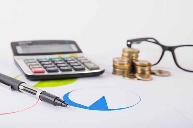 Calculadora com moedas na mesa Foto gratuita
