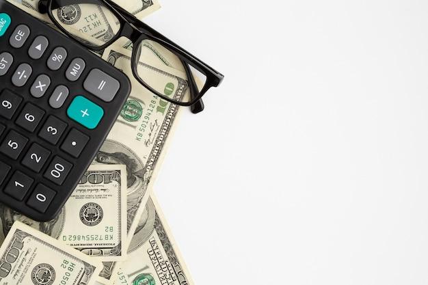 Calculadora em cima de notas de dólar com cópia-espaço Foto gratuita