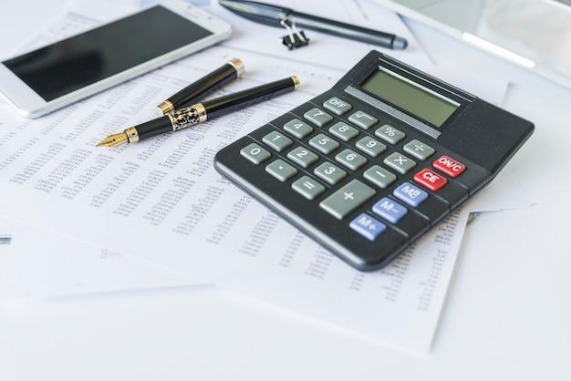Calculadora na mesa com documentos e smartphone Foto Premium