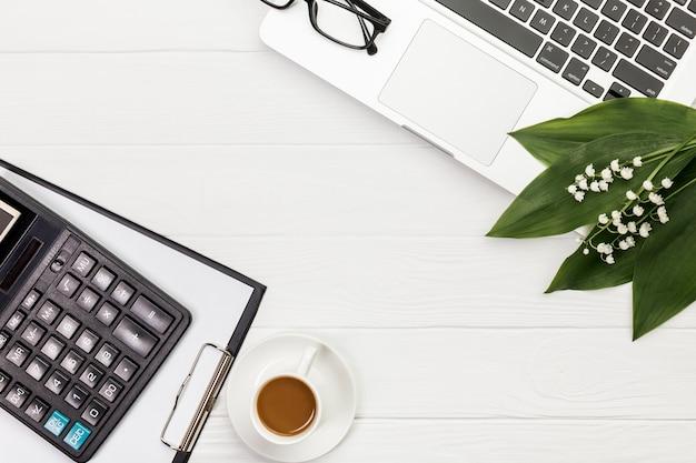 Calculadora, prancheta, xícara de café, óculos e laptop na mesa branca Foto gratuita