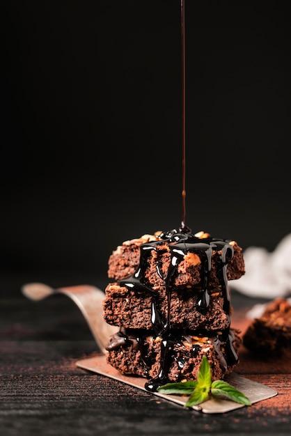Calda de chocolate derramada sobre a torre de brownies de chocolate porca na bandeja Foto gratuita