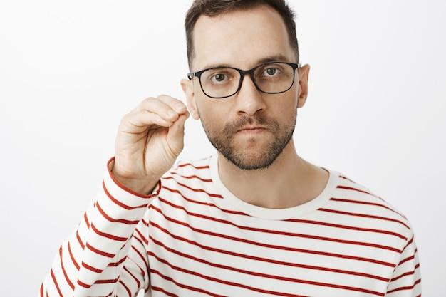 Cale a boca. retrato de um namorado furioso de óculos escuros, chupando os lábios e franzindo a testa, mostrando gesto de silêncio, sentindo-se indignado Foto gratuita