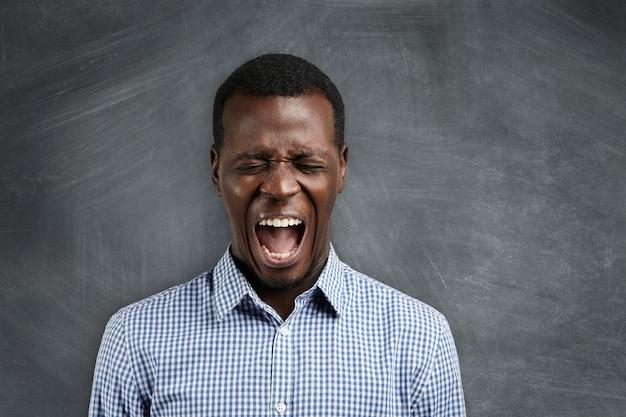Cale-se! foto de um professor de ensino médio africano irritado e furioso gritando com seus alunos desobedientes, pedindo silêncio, com os olhos fechados e a boca bem aberta. Foto gratuita