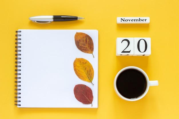 Calendário 20 de novembro xícara de café, bloco de notas com caneta e folha amarela em amarelo Foto Premium