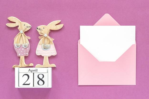 Calendário 28 de abril, par coelhinhos da páscoa de madeira, envelope rosa Foto Premium