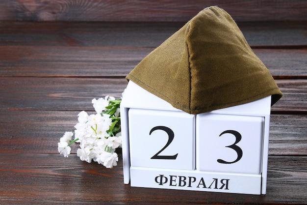 Calendário branco com texto em russo: 23 de fevereiro. feriado é o dia do defensor da pátria. Foto Premium