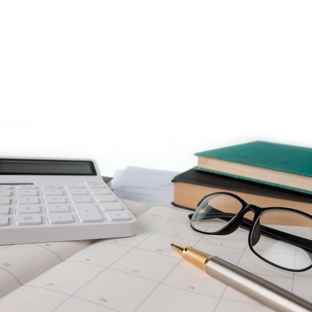 Calendário, calculadora, óculos, caneta e cadernos Foto Premium