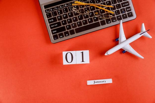 Calendário de 01 de janeiro com acessórios na mesa de escritório de espaço de trabalho de negócios no teclado do computador, avião, óculos fundo vermelho Foto Premium
