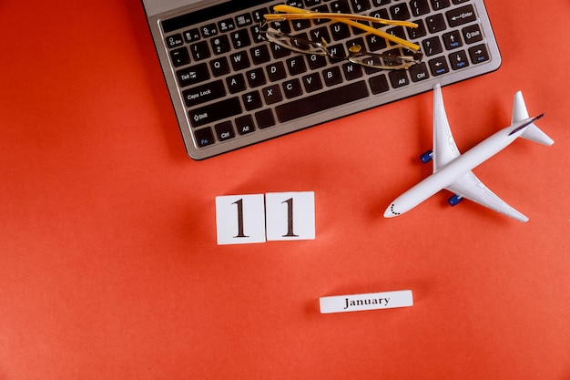 Calendário de 11 de janeiro com acessórios na mesa de escritório de espaço de trabalho de negócios no teclado do computador, avião, óculos fundo vermelho Foto Premium
