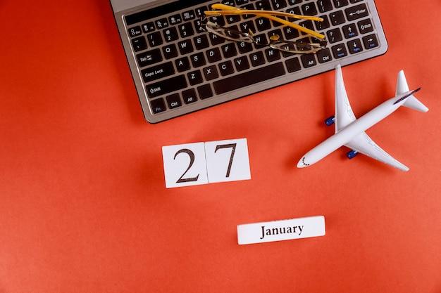 Calendário de 27 de janeiro com acessórios na mesa de escritório de espaço de trabalho de negócios no teclado do computador, avião, óculos fundo vermelho Foto Premium