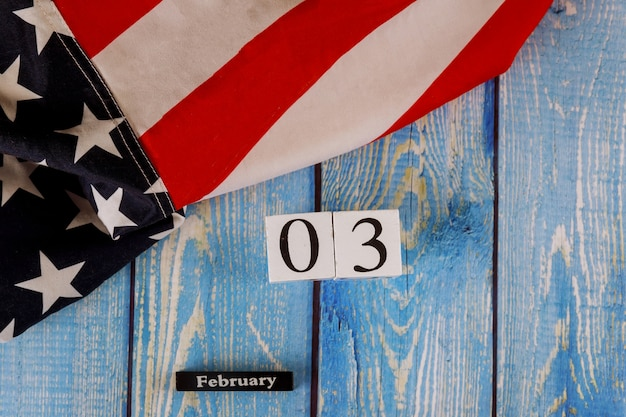 Calendário de 3 de fevereiro, maravilhosamente acenando estrelas e listrada bandeira americana na prancha de madeira velha. Foto Premium