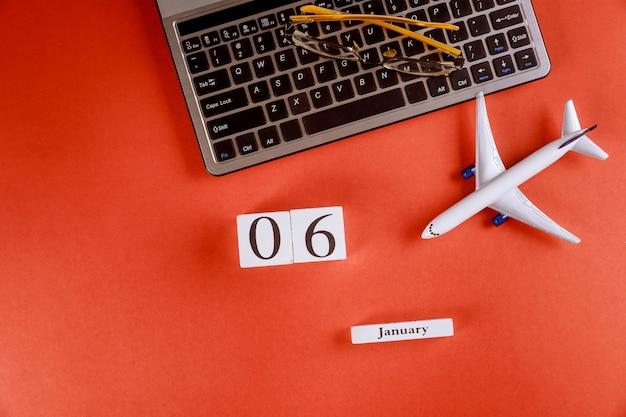 Calendário de 6 de janeiro com acessórios na mesa de escritório de espaço de trabalho de negócios no teclado do computador, avião, óculos fundo vermelho Foto Premium