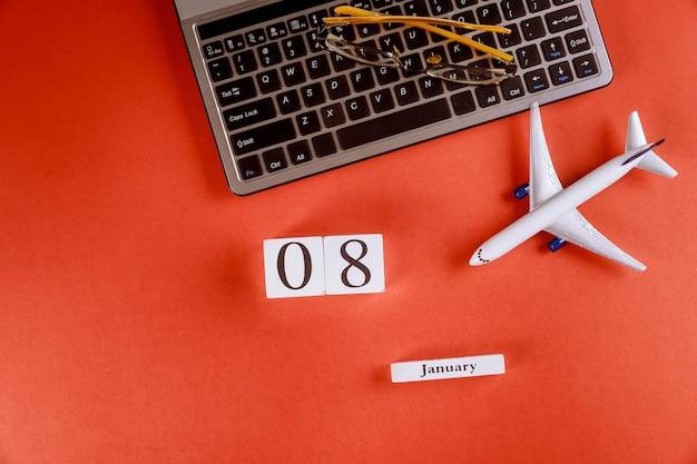 Calendário de 8 de janeiro com acessórios na mesa de escritório de espaço de trabalho de negócios no teclado do computador, avião, óculos fundo vermelho Foto Premium