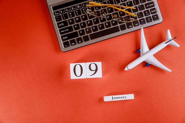 Calendário de 9 de janeiro com acessórios na mesa de escritório de espaço de trabalho de negócios no teclado do computador, avião, óculos fundo vermelho Foto Premium