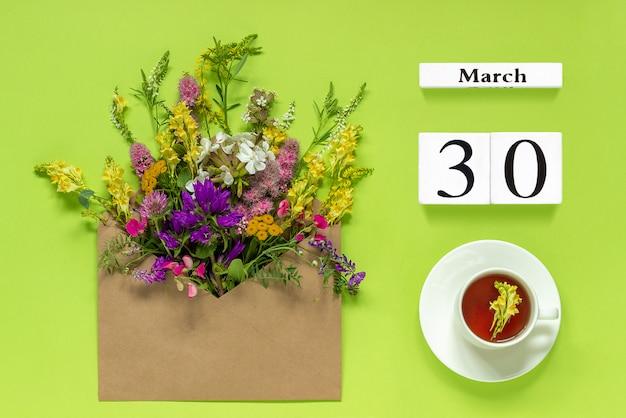 Calendário de cubos brancos 30 de março.corte de chá, envelope kraft com multi colorido flores em verde Foto Premium