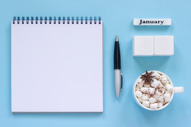 Calendário de janeiro xícara de cacau e marshmallow, bloco de notas aberto vazio mock up Foto Premium