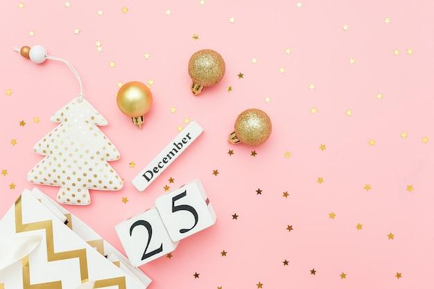Calendário de madeira 25 de dezembro, árvore de natal de têxteis, enfeites dourados, estrelas confetes em rosa. conceito de feliz natal. Foto Premium