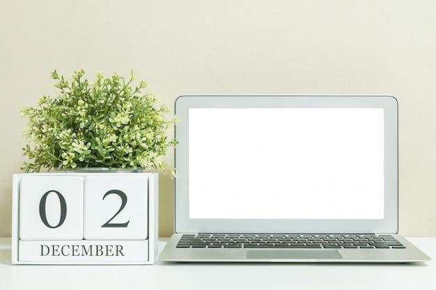 Calendário de madeira branco com preto 2 de dezembro palavra com espaço em branco branco no centro do computador notebook na mesa de madeira branca Foto Premium