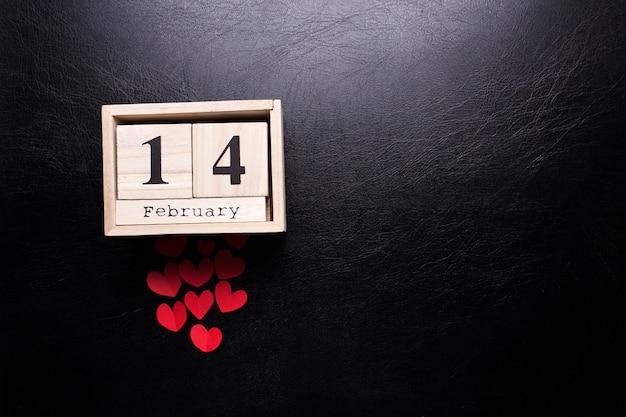 Calendário de madeira com a inscrição em 14 de fevereiro e com pequenas corações em um fundo preto e isolado. Foto Premium