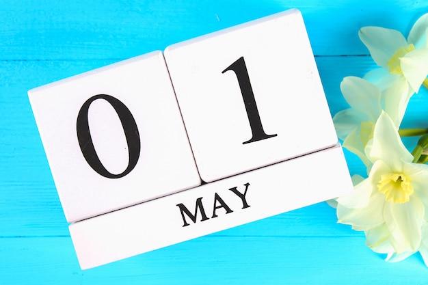Calendário de madeira com o texto: 1 de maio. flores brancas de narcisos. dia do trabalho e primavera Foto Premium