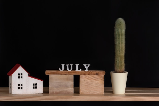 Calendário de madeira de julho, modelo de cacto e casa em fundo preto. copie o espaço. Foto Premium