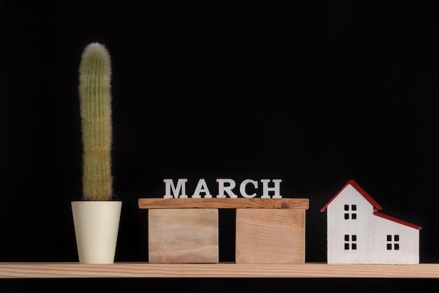 Calendário de madeira de março, modelo de cacto e casa em fundo preto. copie o espaço. Foto Premium