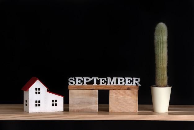 Calendário de madeira de setembro, modelo de cacto e casa em fundo preto. copie o espaço. Foto Premium