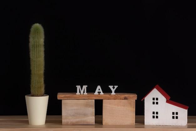 Calendário de madeira do modelo de maio, cacto e casa em fundo preto. copie o espaço. Foto Premium