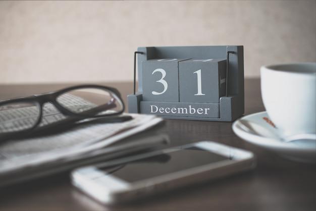 Calendário de madeira vintage para dia 31 de dezembro na mesa de escritório com óculos de leitura de jornal Foto Premium