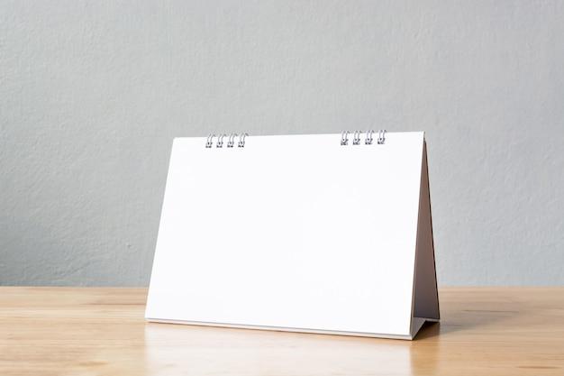Calendário de mesa em branco na mesa de madeira. Foto Premium