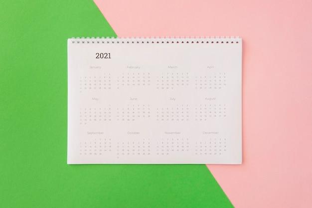 Calendário de mesa plano sobre fundo colorido Foto gratuita