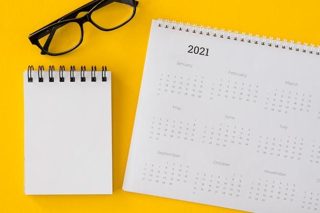 Calendário de vista superior com bloco de notas e óculos Foto gratuita