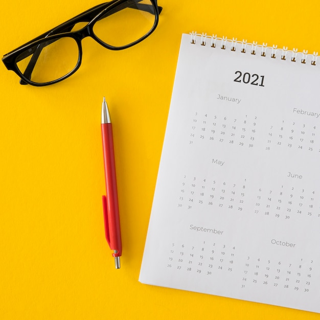 Calendário plano e óculos de leitura Foto gratuita