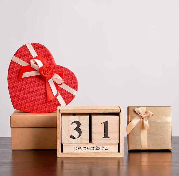 Calendário retrô de madeira de blocos, árvore decorativa de natal e caixas de papelão Foto Premium