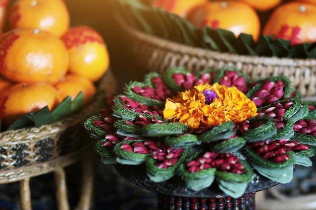 Calêndula e rosa flores em vaso feito de folha de bananeira na arte tailandesa tradicional Foto Premium