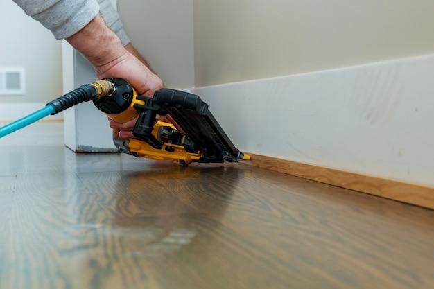 Calibre finish nailer homem pregado slats costume casa edifício contratante até uma seção de parede de luxo Foto Premium
