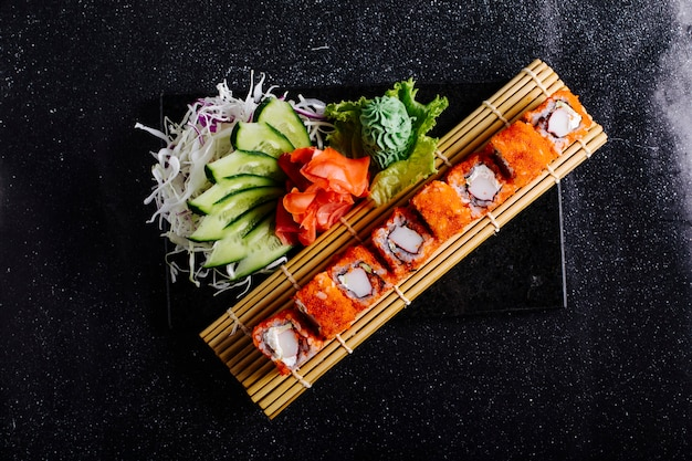 Califórnia quente rola na esteira de sushi com wasabi, gengibre vermelho e pepino. Foto gratuita