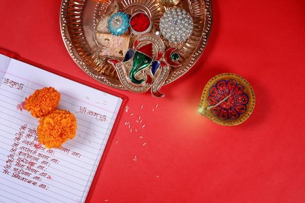 Caligrafia escrita em hindi shubha labh significa bondade & riqueza, sobre livro de contabilidade vermelho, diya, Foto Premium