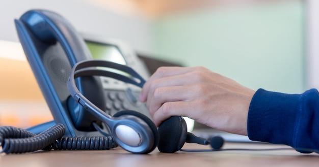 Call center empregado homem mão segurando o fone de ouvido no telefone Foto Premium