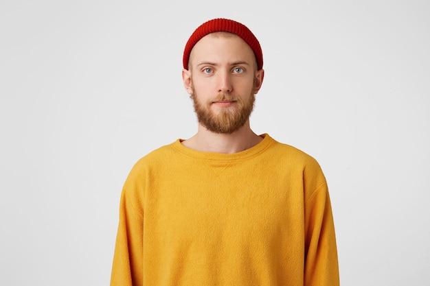 Calma interessante cara barbudo hippie com chapéu vermelho e expressão facial normal Foto gratuita