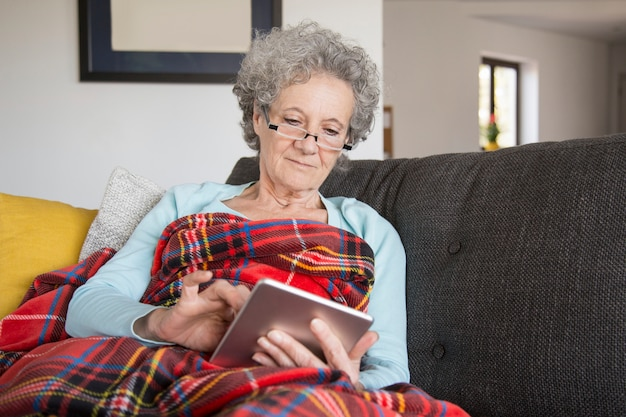 Calma mulher sênior lendo livro on-line com curiosidade Foto gratuita