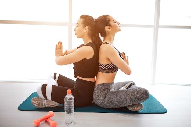 Calmas e concentradas jovens sportgirls sentam-se com as pernas cruzadas e meditam Foto Premium