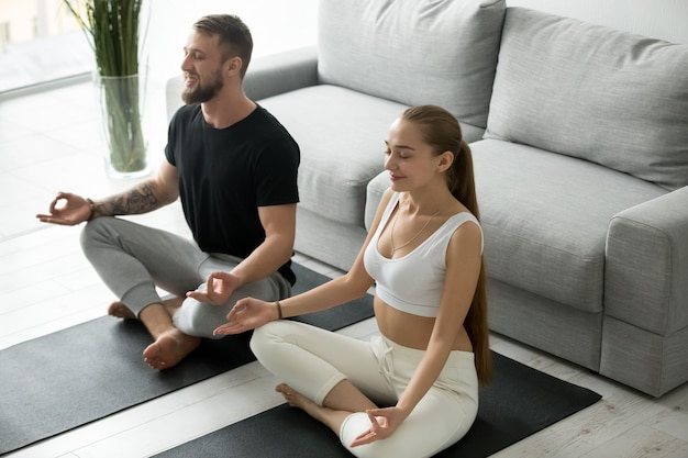 Calmo casal milenar meditando na posição de lótus em casa Foto gratuita