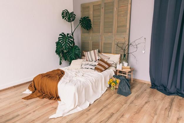 Cama com cobertores e travesseiros em um quarto. interior do quarto. loft Foto Premium